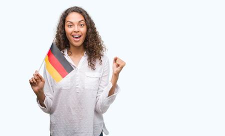 Young hispanic woman holding flag of Germany screaming proud and celebrating victory and success very excited, cheering emotion