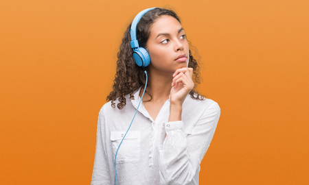 Young hispanic woman wearing headphones serious face thinking about question, very confused idea