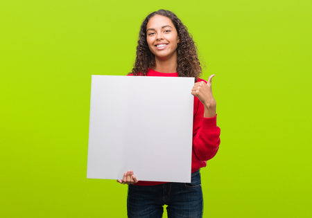 Young hispanic woman holding blank banner happy with big smile doing ok sign, thumb up with fingers, excellent sign
