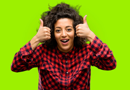Beautiful arab woman smiling broadly showing thumbs up gesture to camera, expression of like and approval Stock Photo