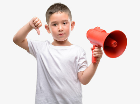 Dark haired little child holding megaphone with angry face, negative sign showing dislike with thumbs down, rejection concept Stock Photo