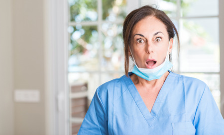 Middle aged doctor woman scared in shock with a surprise face, afraid and excited with fear expression Archivio Fotografico - 104954662