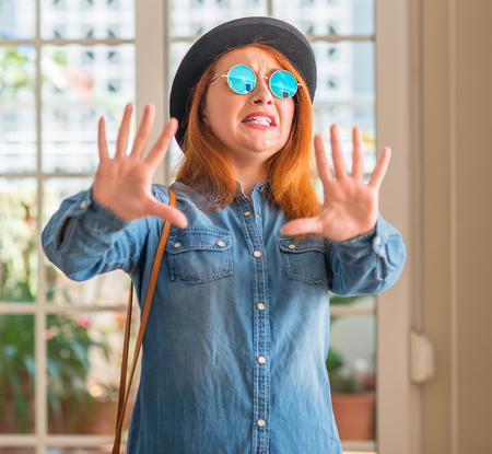 Stylish redhead woman wearing bowler hat and sunglasses afraid and terrified with fear expression stop gesture with hands, shouting in shock. Panic concept.
