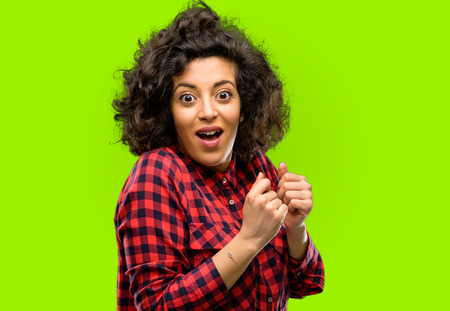 Beautiful arab woman happy and surprised cheering expressing wow gesture Stock Photo
