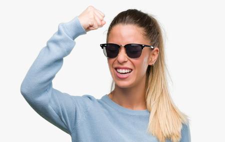 Bella giovane donna che indossa occhiali da sole e coda di cavallo infastiditi e frustrati gridando di rabbia, pazzo e urlando con la mano alzata, concetto di rabbia