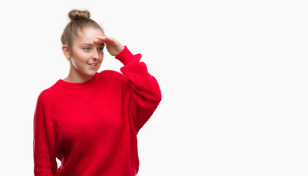 Young blonde woman wearing bun and red sweater very happy and smiling looking far away with hand over head. Searching concept.