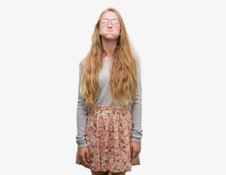 Blonde teenager woman wearing flowers skirt puffing cheeks with funny face. Mouth inflated with air, crazy expression. Stock Photo