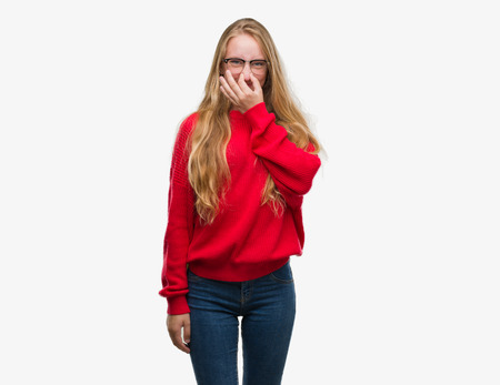 Blonde teenager woman wearing red sweater smelling something stinky and disgusting, intolerable smell, holding breath with fingers on nose. Bad smells concept.