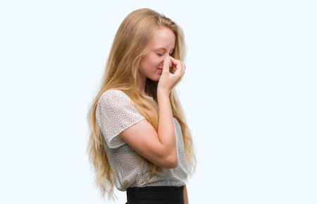 Blonde teenager woman wearing moles shirt tired rubbing nose and eyes feeling fatigue and headache. Stress and frustration concept. Stock Photo