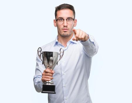 Apuesto joven sosteniendo el trofeo apuntando con el dedo a la cámara y a usted, signo de la mano, gesto positivo y seguro desde el frente