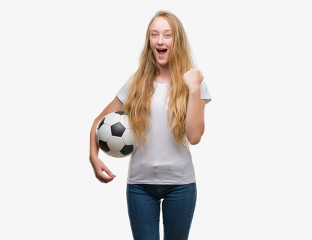 Blonde teenager woman holding soccer football ball screaming proud and celebrating victory and success very excited, cheering emotion