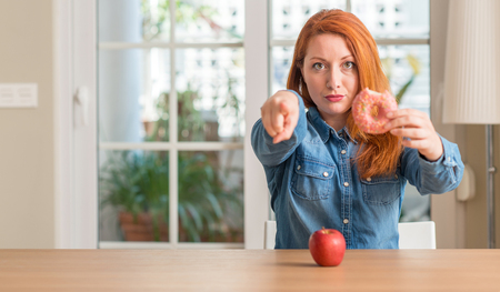 Redhead woman chooses between apple and donut pointing with finger to the camera and to you, hand sign, positive and confident gesture from the front