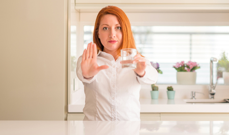 Thirsty redhead woman and glass of water with open hand doing stop sign with serious and confident expression, defense gesture