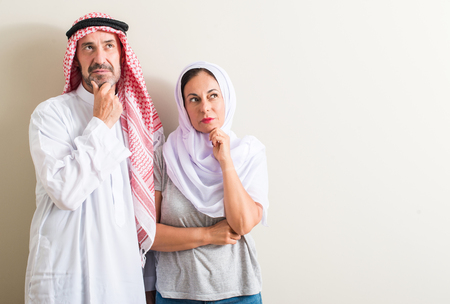 Middle age arabic couple, woman and man serious face thinking about question, very confused idea