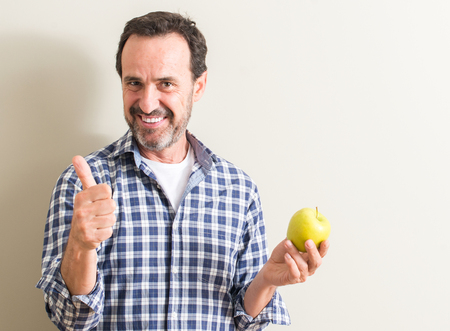 Senior man holding a green apple happy with big smile doing ok sign, thumb up with fingers, excellent sign