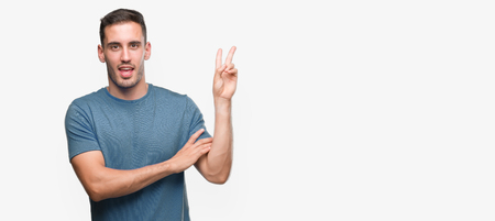 Handsome young casual man smiling with happy face winking at the camera doing victory sign. Number two. Stock Photo