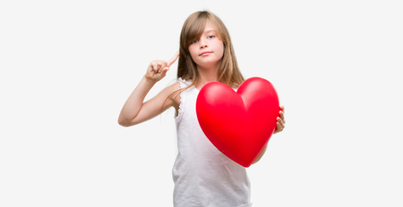 Young blonde toddler holding a red heart surprised with an idea or question pointing finger with happy face, number one Stock Photo