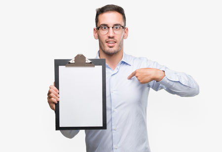 Handsome young business man showing a clipboard with surprise face pointing finger to himself