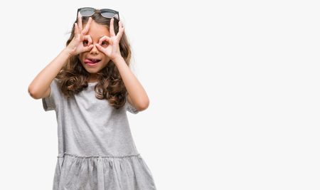 Brunette hispanic girl wearing sunglasses doing ok gesture like binoculars sticking tongue out, eyes looking through fingers. Crazy expression. Banco de Imagens