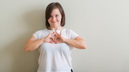 Femme trisomique debout sur le mur souriant amoureux montrant le symbole du cœur et la forme avec les mains. Concept romantique.
