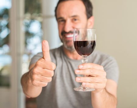 Middle age man drinking a glass of wine happy with big smile doing ok sign, thumb up with fingers, excellent sign 스톡 콘텐츠