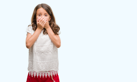 Brunette hispanic girl shocked covering mouth with hands for mistake. Secret concept.