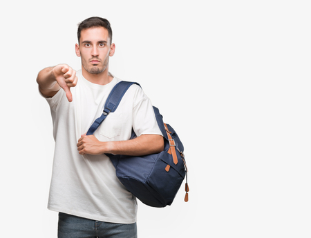Handsome young man holding backpack with angry face, negative sign showing dislike with thumbs down, rejection concept
