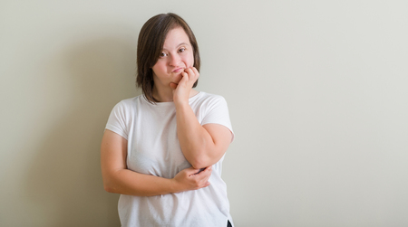 Down syndrome woman standing over wall looking stressed and nervous with hands on mouth biting nails. Anxiety problem. Archivio Fotografico