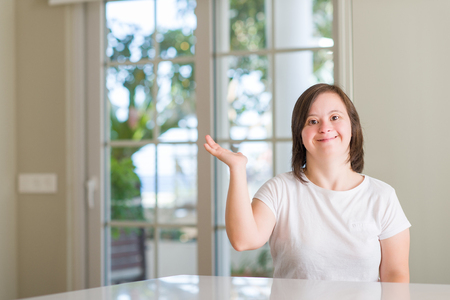 Down syndrome woman at home smiling cheerful presenting and pointing with palm of hand looking at the camera.
