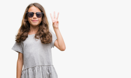 Brunette hispanic girl wearing sunglasses showing and pointing up with fingers number three while smiling confident and happy.