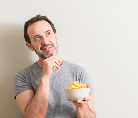 Senior man eating potato chips serious face thinking about question, very confused idea