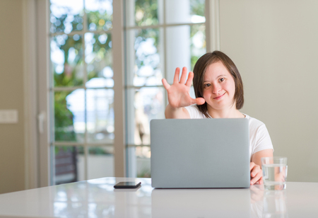 Down syndrome woman at home using computer laptop with open hand doing stop sign with serious and confident expression, defense gesture