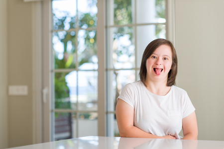 Down syndrome woman at home sticking tongue out happy with funny expression. Emotion concept. Banque d'images