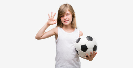 Young blonde toddler holding football ball doing ok sign with fingers, excellent symbol