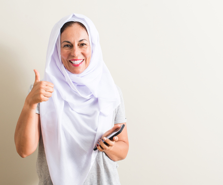 Arabian woman using smartphone happy with big smile doing ok sign, thumb up with fingers, excellent sign