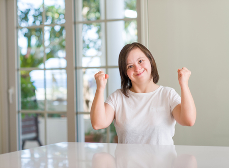 Down syndrome woman at home screaming proud and celebrating victory and success very excited, cheering emotion