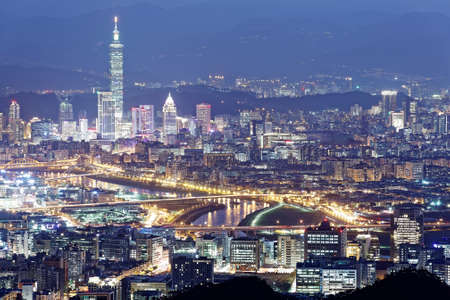 Aerial panorama of Taipei City at dusk with view of bridges over Keelung River & Taipei 101 Tower among skyscrapers in Xinyi District Downtown~ A romantic night of a busy city in a gloomy blue mood