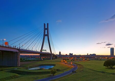 Scenery of the riverside park by Tamsui River with a pathway thru the green grassy meadow & the grand bridge tower standing tall under beautiful sunset sky in New Taipei City, Taiwan (Low Angle View ) 版權商用圖片