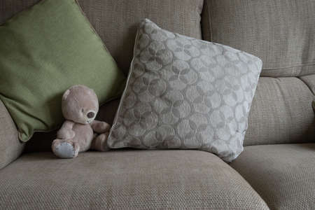 complimentary: small stuffed bear on a couch, complimentary palette, interior design inspiration