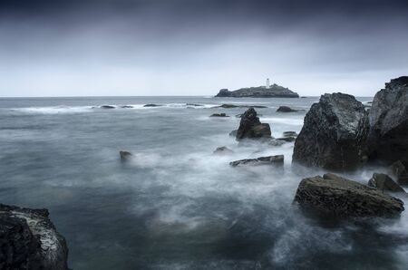 A long exposure of a stormy sea around Godrevy lighthouse, Gwithian, Cornwall, England Stockfoto - 131440474