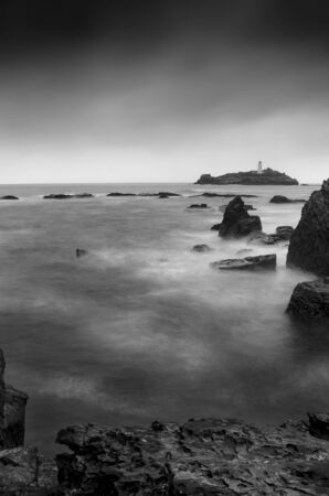 A long exposure of a stormy sea around Godrevy lighthouse, Gwithian, Cornwall, England