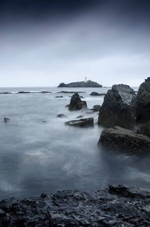 A long exposure of a stormy sea around Godrevy lighthouse, Gwithian, Cornwall, England Stockfoto - 131440524