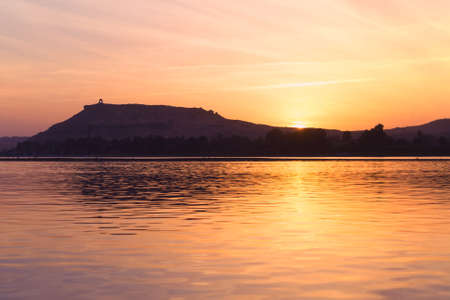 A tranquil sunset shot over the River Nile, from aboard a Felucca in Aswan, Egypt. Stock Photo