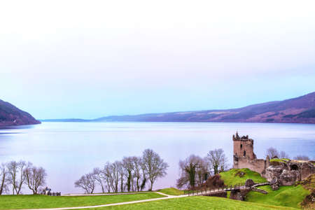 Hazy midday skies over Urquhart Castle at Loch Ness in Scotland, UK.