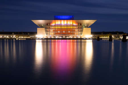 A long, low-light exposure of Copenhagen Opera House, Denmark. The colours from the building at night reflect beautifully across the water.