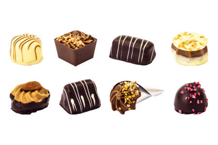 A diverse mix of eight different sweet chocolates produced by a creative chocolatier and presented on a white background, isolated for use by designers and other users. Stock Photo