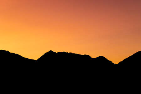 The silhouetted mountains surrounding Pemberton in British Columbia stand in stark contrast to the vibrant orange, yellow and red stained sky during Sunset in late Summer.