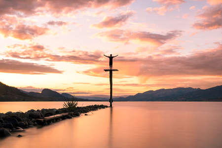 Photographer Aaron Northcott poses for a silhouette photograph atop a large platform as the Sun sets over lake Okanagan in Penticton, British Columbia, Canada. The Sunlight casts orange and purple light across the surface of the lake and illuminates mountains in the distance and clouds high in the sky.