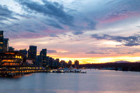 An incredible Sunset illuminates the Summer sky over Vancouver, BC silhouetting the cityscape as the lights of buildings, street lamps, cars, boats and planes glow softly in the twilight; as seen from Canada Place.