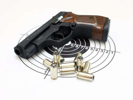 The close up of a pistol a target and cartridges is isolated on a white background photo